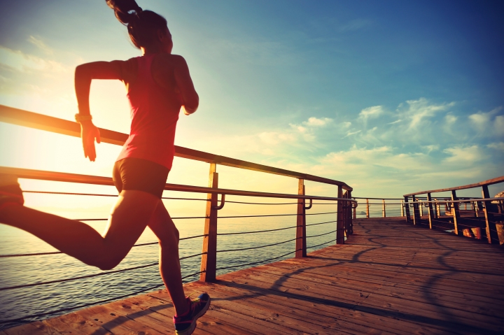 healthy lifestyle sports woman running on wooden boardwalk sunri